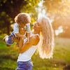beautiful young mother with her son having fun in a park