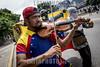 """Venezuela - Caracas 22 de julio, la Guardia Nacional Bolivariana dispara perdigones y hace la """"gestos""""con la mano durante la marcha de protesta al TSJ para intentar dispersar a los manifestantes. Hasta finales de horas de la tarde se presentaron fuertes enfrentamientos en varios sectores de la capital en otra jornada de manifestaciones contra el régimen de Nicolás Maduro y su llamado a una Constituyente. Protests in Caracas on July 22th against Nicolás Maduro regime.  / Venezuela :  Ausschreitungen am 22. Juli 2017 in Caracas - Demonstranten der Opposition  kämpfen auf der Strasse gegen den Polizeieinsatz der Regierung Maduros - Inmitten der Demonstranten spielt ein Mann umhüllt mit der Nationalflagge Geige © Leo Álvarez /LATINPHOTO.org"""