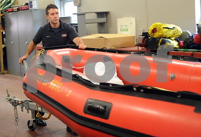 Robert Layman / Staff Photo Rutland City Firefighter Nate Elwert moves a rescue boat in the Rutland City Fire Department's garage Thursday afternoon.