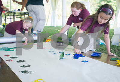 Robert Layman / Staff Photo Christ the King students paint with sunflowers on a large sheet of paper duing the Come Alive Outside Event at the Rutland Regional Medical Center Wednesday, September 28, 2017.