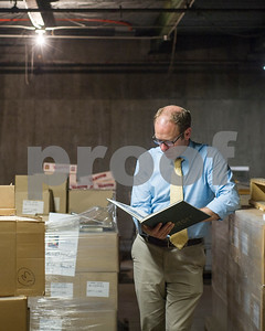 Robert Layman / Staff Photo Robert R. Mitchell, Rutland Herald General Manager, looks through boxes of archived materials in the basement of the publication's offices Wednesday September, 28, 2017.