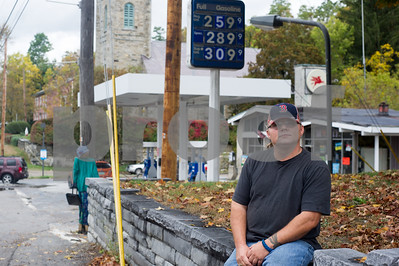 Robert Layman / Staff Photo Henry Allen sits on a stone wall outside a Mobil station he was one employed at in downtwon Brandon, October 9, 2017. After getting the news that the gas station, which is the only full service station in the area, was being sold to Casella Construction, Allen started a petition to keep it open.