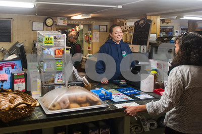 Robert Layman / Staff Photo Jesse Bridge checks out a regular while making small talk at her store Thursday morning. Bridge usually works the opening shift, which starts at 5 a.m.  and said isn't uncommon to work until close at  6 p.m.