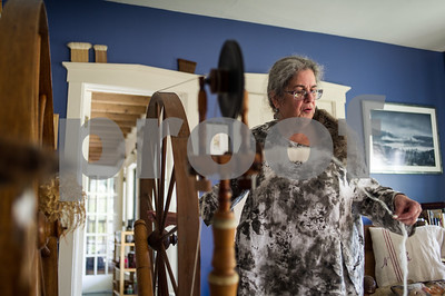 Robert Layman / Staff Photo Middletown Srpings resident Nora Rubinstein pulls fiber from an old spinning wheel in her home Thursday. Rubinstein has been researching large spinning wheels she beleives to have been crafted by Samuel Morison, a wheel maker with ties to the Wallingford and Danby areas from 1800s. this wheel is beleived to be one of Morisons.