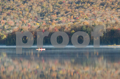 Robert Layman / Staff Photo A pair of kayakers work their way around the Chittenden Reservior as mist rises  and the fading foilage is reflected in its waters Thursday morning.