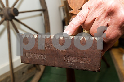 Robert Layman / Staff Photo Nora Rubinstein points to one of the stamped insignias on a wheel she believes to be crafted by Samuel Morison in the 1800s at her home in Middletown Springs Thursday afternoon. In addition to the stamp, there were also the indented teeth marks where her finger points to that are specific to spinning wheels beleived to be crafted by Morison.