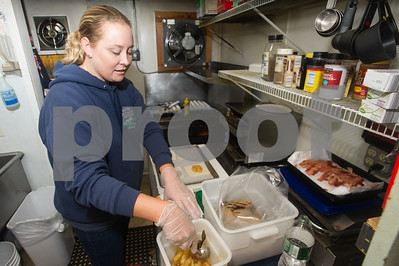 Robert Layman / Staff Photo Jesse Bridge prepares some apple turnovers in her store's kitchen Thursday morning. Bridge says one of the things that separates her from other country stores in the freshly made breakfast sandwiches her regulars rely on before work.