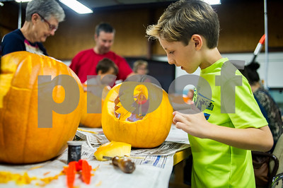 """Robert Layman / Staff Photo  Keenan Oberkirch, 7, fits an LED light into his """"Steal Your Face"""" themed pumpkin while carving with his brother, father and others at The MINT in Rutland Wednesday night, October 25, 2017. """"Steal Your Face"""" is an album released by the famous jam band The Greatful Dead in 1976, and its album art has served as an emblematic logo for the band decades after its relase."""