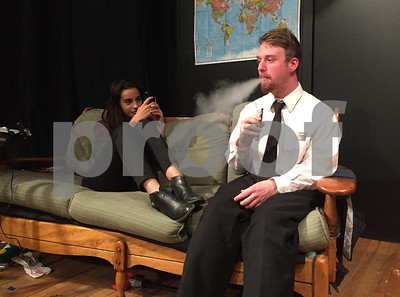Robert Layman / Staff Photo Ellie, left, played by Maya G. Redington, videotapes Elder Thomas, played by Eric Ray, as he takes a hit from a vaporizer.