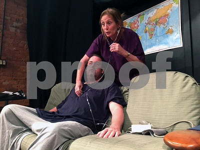 Robert Layman / Staff Photo  Charlie, left, played by Matthew Riley, gets his blood pressure checked by his hospice nurse, Liz, played by Diane Laccardi.