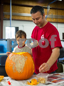 Robert Layman / Staff Photo  Theo Gile, left, 3, and his father Rick dig pumpkin seeds out during a carving party at the MINT in Rutland Wednesday night, October 25, 2017. This was Theo's first time carving, and he was not sure what he was going to craft.