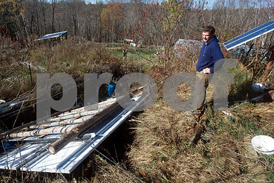 """Robert Layman / Staff Photo Josh Squier, co-owner of Breezy Meadow Orchards, stands next to a 4kw photovoltaic array that was destroyed by the wind storm last week. """"We got off lucky,"""" Squier said while explaining the damage. The day of the windstorm, which ran from Sunday October 29 to early October 30, Squier and his wife Meadow had just finished putting end walls on their new green houses. Without the end walls, the greenhouses would have met the same fate as the solar array, Squier said. The array had survived other extreme weather events in the past, but Squier believed the wet ground loosened the ground's hold. Breezy Meadow Orchards is an off grid operation and gets all their energy from solar panels, which Suqier cites is another reason the farm got off lucky. """"Now that it's cold we don't have to worry about running the walk-in cooler,"""" he said. With labor and supplies, Squier estimates that the overall damage is $13,000."""