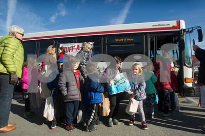 Robert Layman / Staff Photo Students from Northwest Elementary School wait eagerly to drop off donations for the The Bus' annual Stuff-A-Bus event which takes donated items brought to the city buses to local food shelves and community outreach centers.
