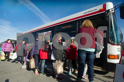 Robert Layman / Staff Photo Students from Northwest Elementary school wait in line, eager to put their donated items on the The Bus during their annual Stuff-A-Bus food drive event Thursday afternoon in the downtown shopping plaza.