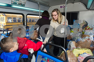 Robert Layman / Staff Photo Courtney Ianni, right, takes donations from Northwest Elementary School students during the annual Stuff-A-Bus event at the downtown shopping plaza Thursday morning.