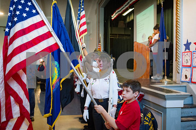 Robert Layman / Staff Photo Doug Walker, right, walks with an American flag in front of the American Legion Post #31 and VFW Post 648 color guards, center, during the Rutland Intermediate School Veterans Day ceremony Thursday.