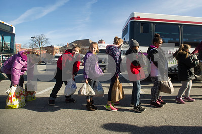 Robert Layman / Staff Photo Northwest Elementary School students wait eagerly in line to drop off their donations for Stuff-A-Bus, The Bus' annual food drive, at the downtown shopping plaza Thursday morning.
