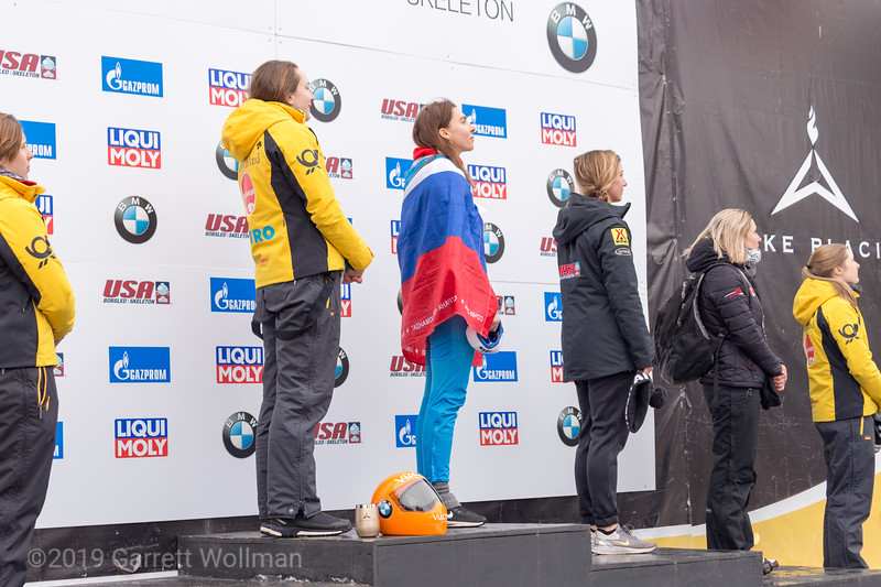 Medalists watching the flag-raising