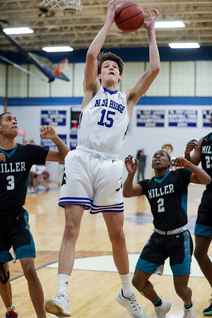PHOTO/ANDREW SHURTLEFF Blue Ridge School's forward Houston Emory (15) grabs a rebound next to Miller School defenders during the game Wednesday night at the Blue Ridge School.