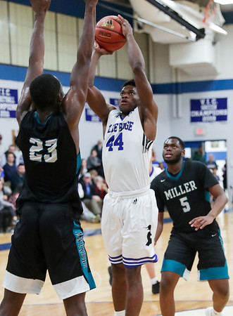 PHOTO/ANDREW SHURTLEFF Blue Ridge School's forward Andrew Nwaoko (44) shoots between Miller School's Tariq Balogun (23) and Miller School's Dae Dae Heard (5) during the game Wednesday night at the Blue Ridge School.