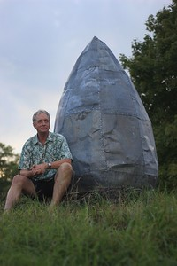 Artist Jay Mead, sits beside one of his sculptures