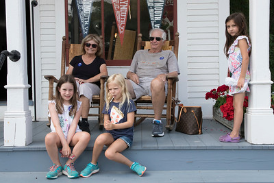 USE_12-Diane_and_Don_Johnson_watched_happenings_from_the_front_porch_of_the_general_store_while_their_granddaughters_Madeline_Lila_and_Marie_enjoyed_some_maple_candies