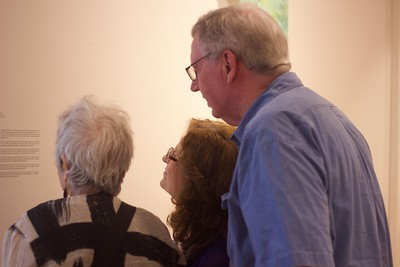 Left to right, Carla Munsat, Nira Fox, and Steve Fox, crowd around an exhibit