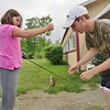 PHOTOS BY jENN SMITH — THE BERKSHIRE EAGLE <br /> Volunteer Nick Gingras helps to retrieve a fish from the line of Casey Haberern, 10, during Saturday's Harry A. Bateman Memorial Jimmy Fund Fishing Derby in Pittsfield.