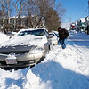 Benjamin Coil of Farmland Rd., in Lowell shoveling out his car. (The Sun / Chris Tierney)