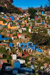 Colorful graves dot the steep hillside