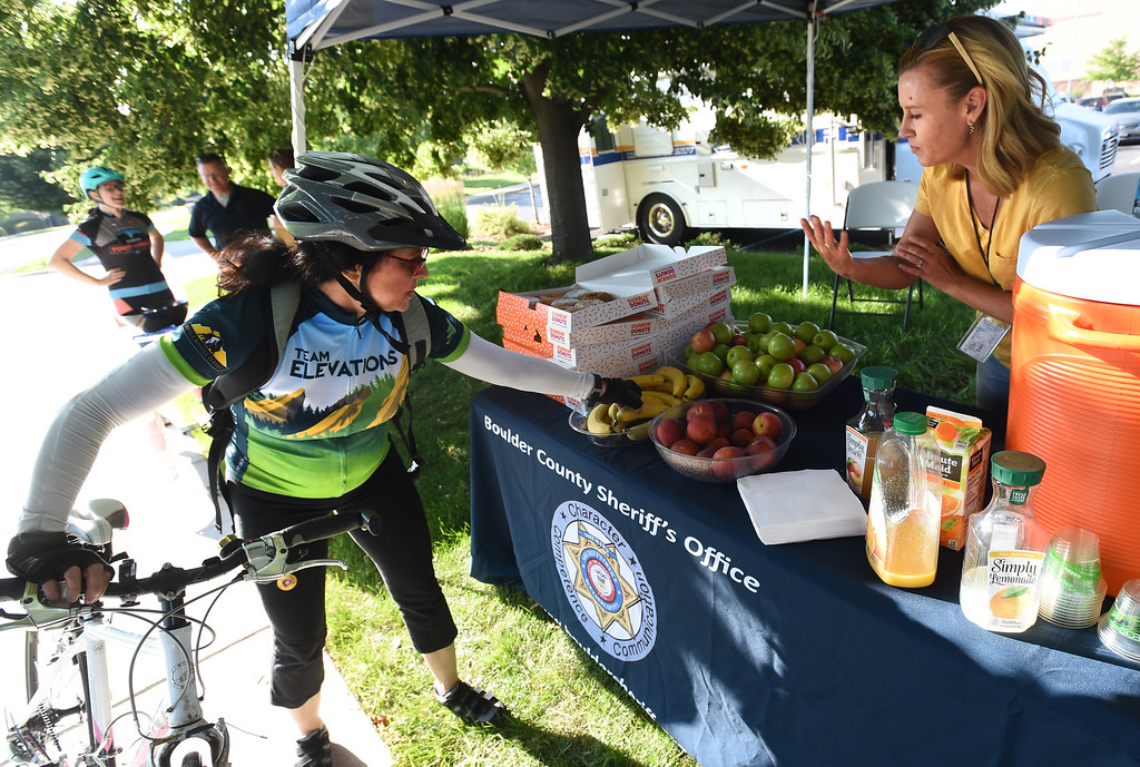 . Alicia Palmer, right, of the Boulder County Sheriff\'s Department, puts out breakfast treats during Boulder\'s Bike to Work Day on Wednesday. For more photos, go to dailycamera.com. Cliff Grassmick  Staff Photographer  June 27, 2018