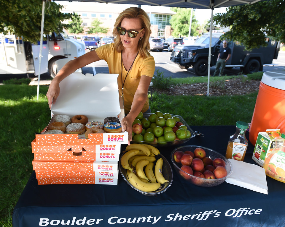 . Alicia Palmer, of the Boulder County Sheriff\'s Department,  puts out breakfast treats during Boulder\'s Bike to Work Day on Wednesday. For more photos, go to dailycamera.com. Cliff Grassmick  Staff Photographer  June 27, 2018