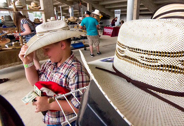 Ten-year-old Kolton Forlines of Shelbyville picks out a cowboy hat at Saturday's second annual Buckin' For Wishes rodeo in Altamont.<br /> Keith Stewart Photo