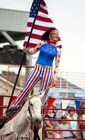 Dusti Crain-Dickerson presents the American flag prior to the National Anthem at Saturday's second annual Buckin' For Wishes rodeo in Altamont.<br /> Keith Stewart Photo