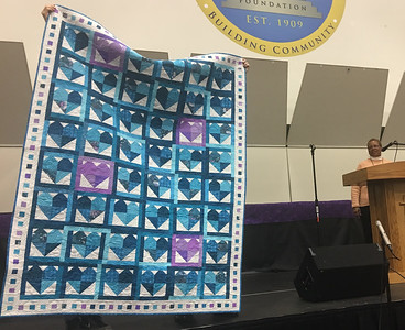 Marie Bard-Curtis showing a quilt for the Teal Quilt project.  Someone else pieced the top and Marie did the machine quilting.