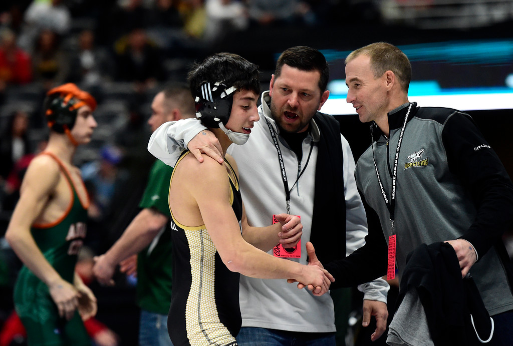 . Monarch High School\'s Ryan Kuykendall is congratulated by Head Coach Ezra Paddock, center, and Assistant Coach Jason Brewer after he won a 5A 113-pound first round match during day 1 of the CHSAA State Wrestling Tournament at the Pepsi Center in Denver. More photos: BoCoPreps.com Jeremy Papasso/ Staff Photographer 02/15/2018