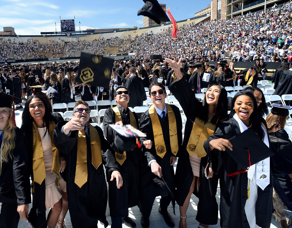 . Ariana Freeman, left, Jake Shapiro, Nathan Tung, Bobby Gehlen, Chanelle Tong, and Brecca Thomas, throw their caps up during the 2018 CU Commencement on May 10, 2018.  For more photos and a video, go to dailycamera.com. Cliff Grassmick  Photographer  May 10,  2018