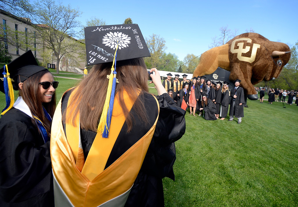 . Nina Perez takes a photo of friends in front of the buffalo during the 2018 CU Commencement on May 10, 2018.  For more photos and a video, go to dailycamera.com. Cliff Grassmick  Photographer  May 10,  2018
