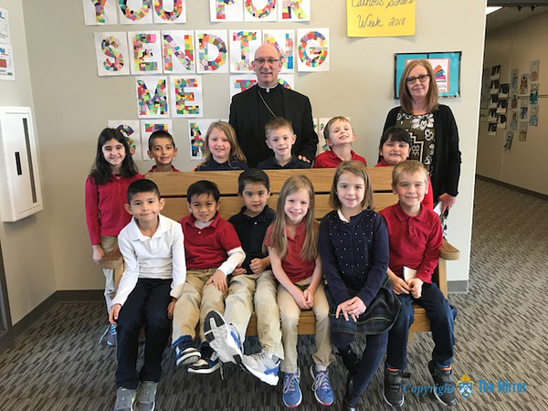 CLASS VISITS—Bishop Edward Rice visited each class during his Catholic School Week visit to St. Mary Catholic School in Joplin on Jan. 29. Here he is with Mrs. Lorrie Estrada's first graders. (<i>The Mirror</i>)