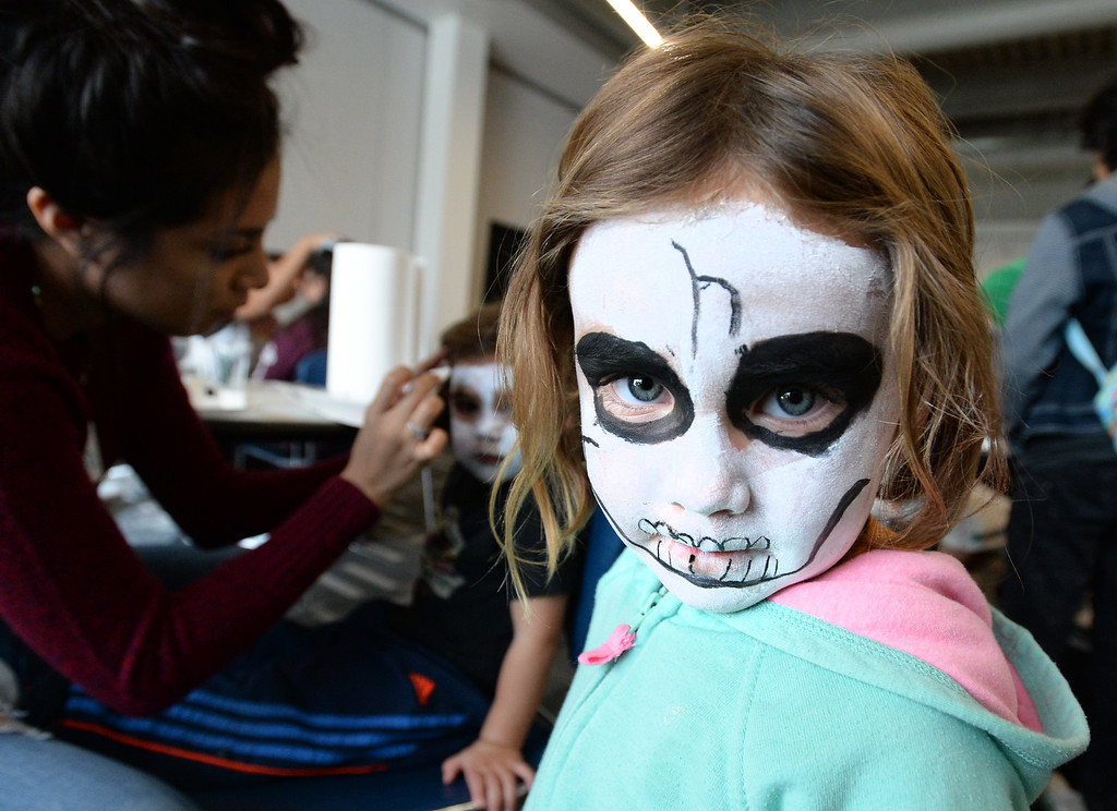 . LONGMONT, CO - November 3, 2018: Itzel Franco, 3, waits for her sister, Nayeli, 2, to get her face painted  by Rocio Monsivais. Longmont�s annual Día de los Muertos celebration is the Longmont Museum�s signature event and the largest Day of the Dead celebration in Colorado, attracting more than 6,000 people to the event.  (Photo by Cliff Grassmick/Staff Photographer)