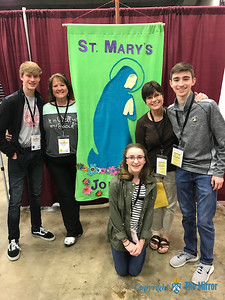 Members of St. Mary Catholic Church, Joplin, stood before their banner. (The Mirror)