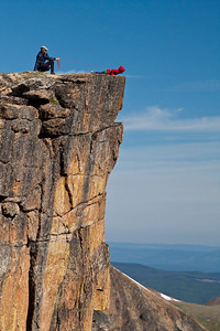 A father holds on tight to a rope while his son looks over the edge of a rocky cliff.