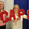 Roger Schneider | The Goshen News<br /> Claire Powell, left, fundraising manager, and Leah Plan, parent aid director, hold up some letters that spell out their agency's name during the trade show portion of the Goshen Founder's Day event Thursday.