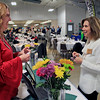 Roger Schneider | The Goshen News  Sheena Whitaker of Greencroft Goshen, left, and Karen Lee of The Award Factory, trade business cards durkng the trade show at the Goshen Founder's Day event Thursday at the Elkhart County 4-H Fairgrounds.
