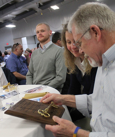 Roger Schneider | The Goshen News<br /> Chris and Carl Weaver, right, look over the Allan J. Kauffman Good of Goshen award Mr. Weaver received Thursday during the Goshen Founders Day event.