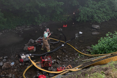 31 Firefighters set up portable pumps right in the Kedron Brook in order to draft water for the pumper trucks