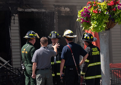 37Fire investigators discuss the possible origin of the fire late Monday morning after poking around in the charred office area of the destroyed PI Brick Oven restaurant on Central Street