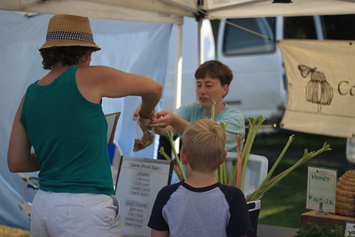 Amy Fredland, and her son Simon are offered rhubarb samples by Jennifer Cary of Contented Butterfly Farm