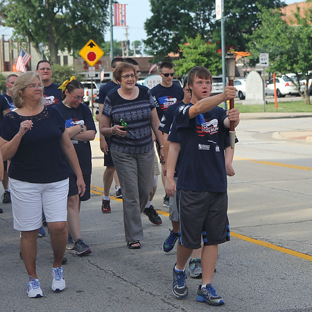 Tom Frichtel of Newton carries the torch during the 16th leg of the Special Olympic's Law Enforcement Torch Run on Wednesday morning in downtown Effingham. The event raises awareness and money for the Special Olympics. The state competitions begin on Friday. Graham Milldrum photo