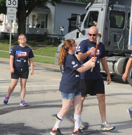Macey Williamson looks on as Angie Haarman passes the torch to a law enforcement officer during the 16th leg of the Special Olympic's Law Enforcement Torch Run started Wednesday morning in downtown Effingham. The event raises awareness and money for the Special Olympics. The state competitions begin on Friday. Graham Milldrum photo